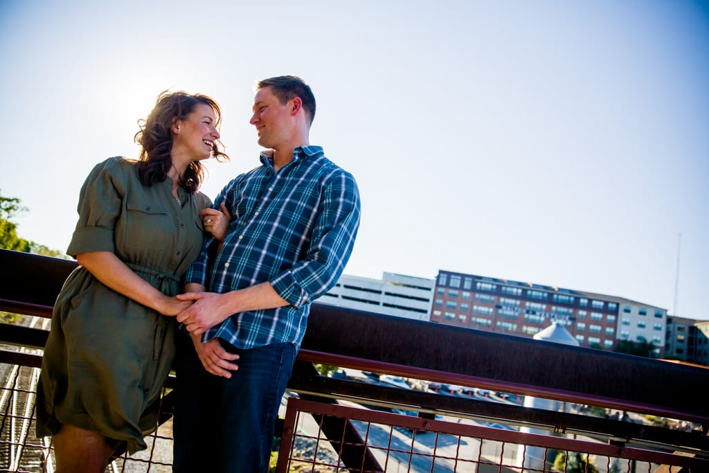 A couple on the bridge at west midtown provisions district take an engagment . portrait