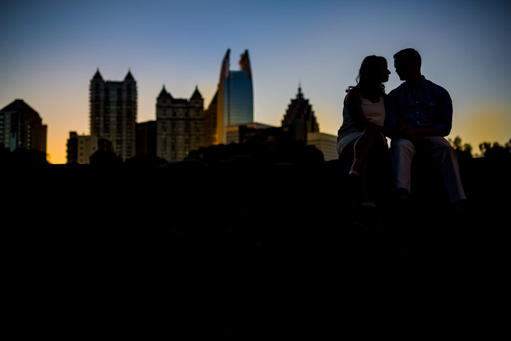 During an engagement session a couple sits in piedmont park with a sunsetting on the skyline behind them.