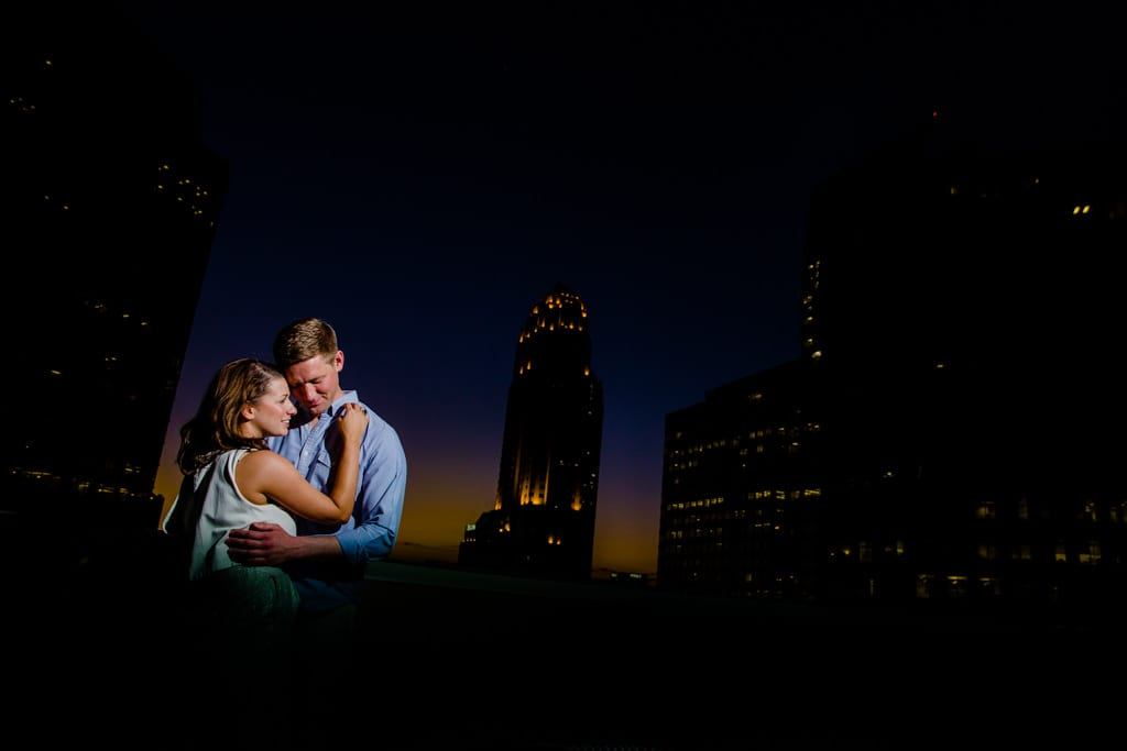 A couple during sunset on a rooftop with the midtown skyline during their engagement session .