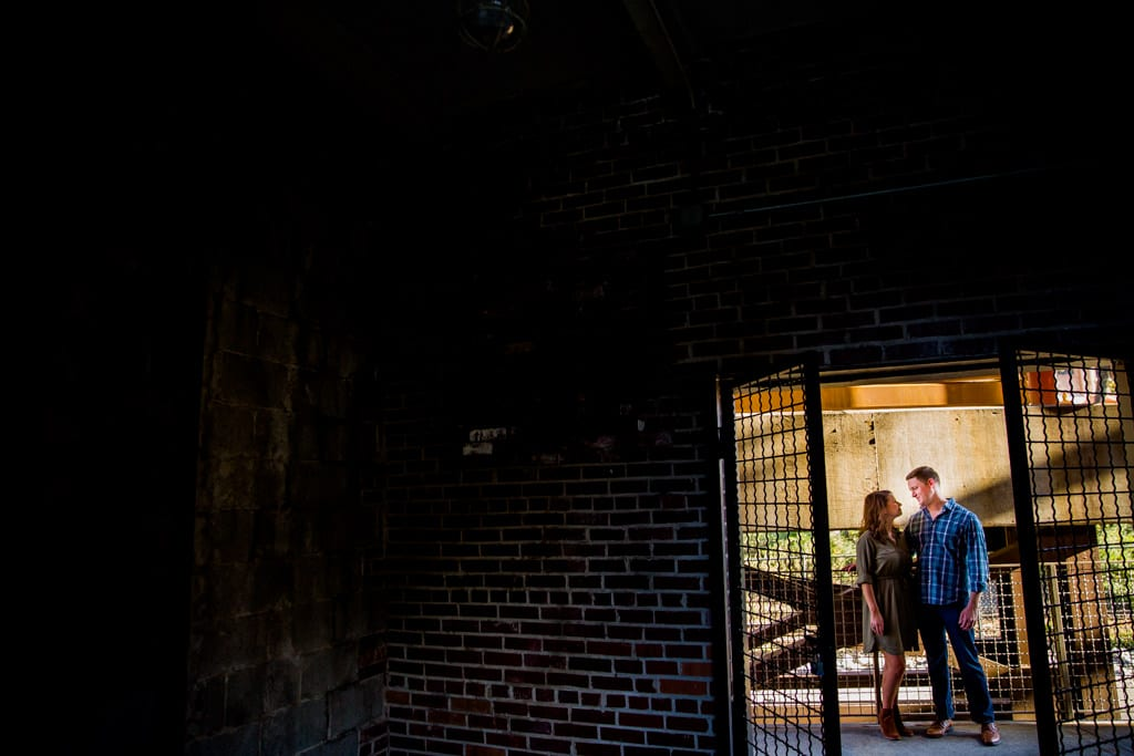 A rustic looking engagement portrait with dramatic light in the westside provisions district in midtown Atlanta.