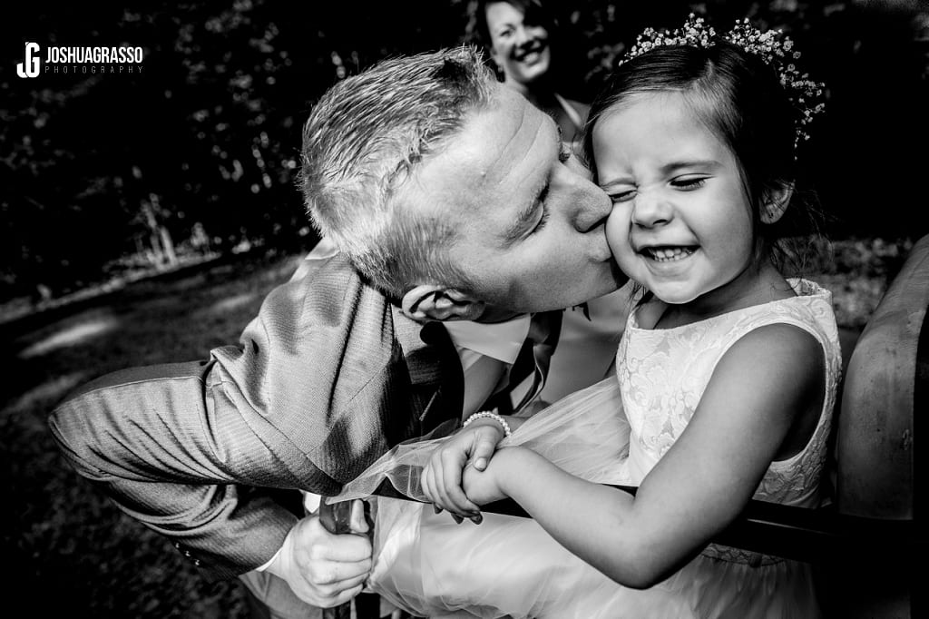 groom kissing flower girl