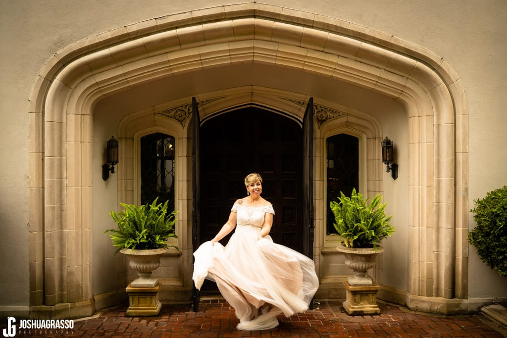 Bride twirling wedding dress in front of callanwolde fine arts center doors