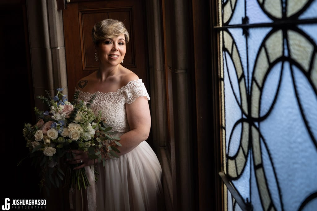 Bride posing for portrait in front of callanwolde fine arts center stained glass