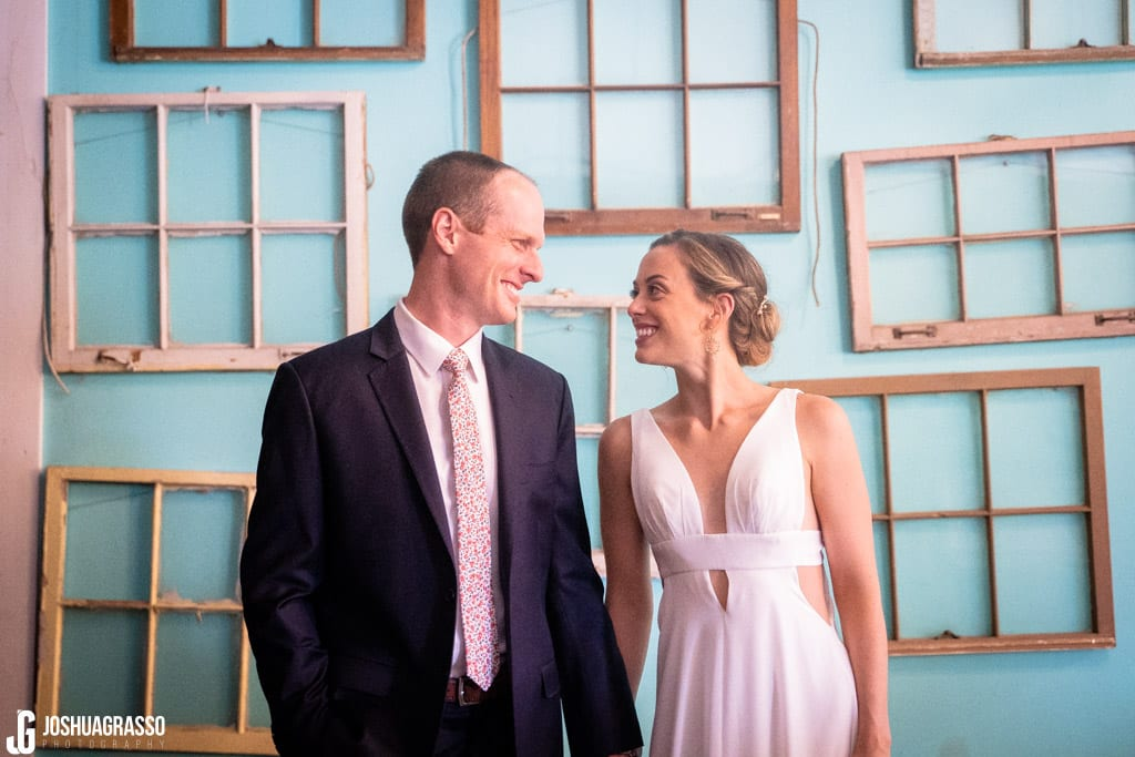 bride and groom in front of window wall at Monday Night Garage Wedding