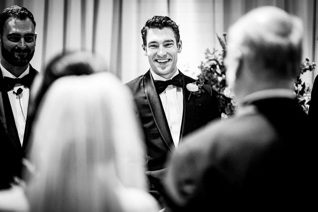 Groom sees bride for the first time in her wedding dress as she walking down the aisle with her dad..
