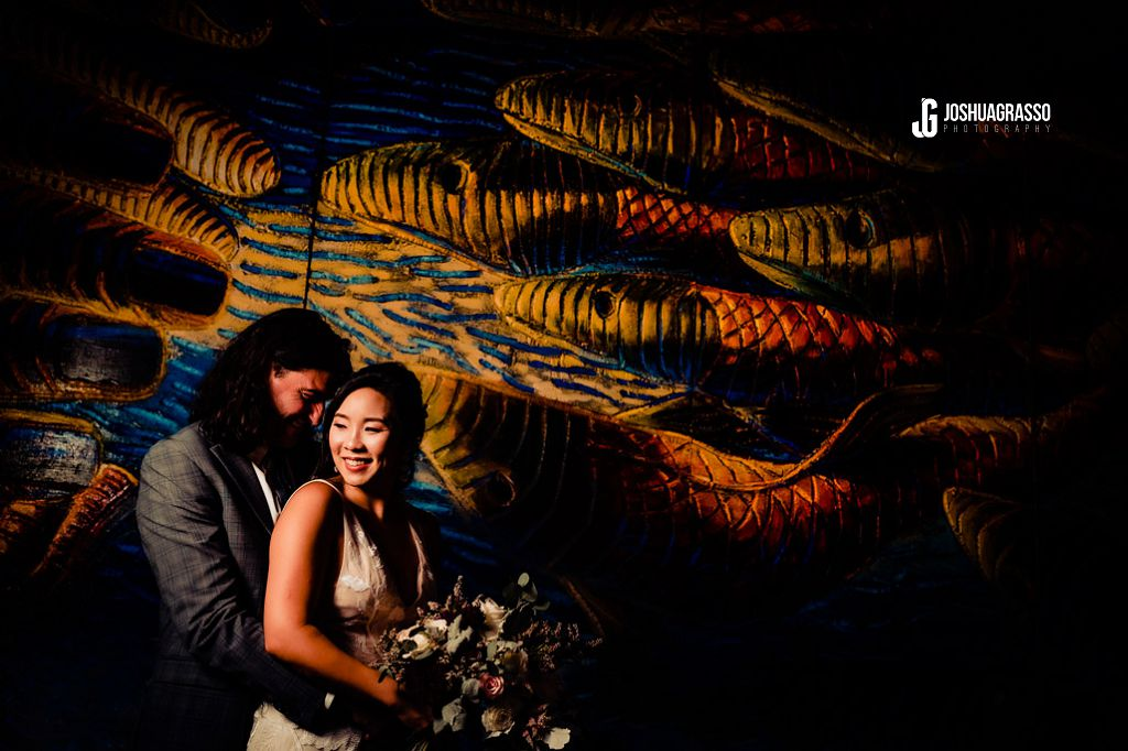 bride and groom portrait at king plow art center in front of artwork